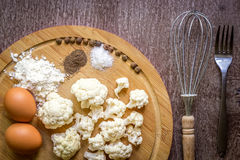Healthy eating, vegetarian food. Raw cauliflower prepared for frying in a frying pan with spices in olive oil. Top view. Wooden background. Copy space. Still Royalty Free Stock Photography