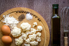 Healthy eating, vegetarian food. Raw cauliflower prepared for frying in a frying pan with spices in olive oil. Top view. Wooden background. Copy space. Still Stock Photography