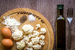 Healthy eating, vegetarian food. Raw cauliflower prepared for frying in a frying pan with spices in olive oil. Top view. Wooden background. Copy space. Still Royalty Free Stock Image