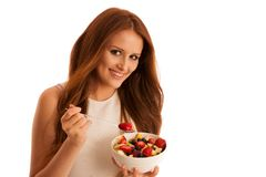 Healthy eating  - woman eats a bowl of fruit salad isolated over. White background - vegetarian meal Stock Photography