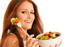 Healthy eating  - woman eats a bowl of greek salad isolated over. White background - vegetarian meal Stock Image