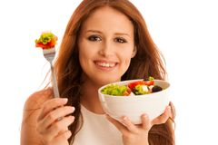 Healthy eating  - woman eats a bowl of greek salad isolated over. White background - vegetarian meal Stock Photography
