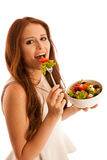 Healthy eating  - woman eats a bowl of greek salad isolated over. White background - vegetarian meal Royalty Free Stock Images
