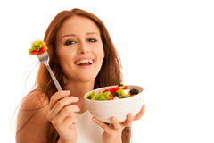 Healthy eating  - woman eats a bowl of greek salad isolated over. White background - vegetarian meal Royalty Free Stock Photo