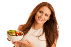 Healthy eating  - woman eats a bowl of greek salad isolated over. White background - vegetarian meal Stock Photo