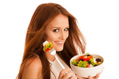Healthy eating  - woman eats a bowl of greek salad isolated over. White background - vegetarian meal Stock Images