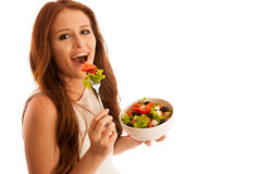 Healthy eating  - woman eats a bowl of greek salad isolated over. White background - vegetarian meal Royalty Free Stock Photos