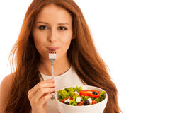 Healthy eating - woman eats a bowl of greek salad isolated over stock photo