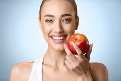 Healthy Eating. Woman Holding Red Apple, Blue Background royalty free stock photos