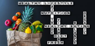 Healthy eating wordcloud or crossword with variety of fresh fruits in brown paper bag. Against dark background royalty free stock images