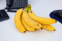Healthy eating at work, bananas on the desk Royalty Free Stock Image