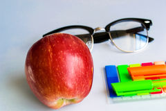 Healthy Education. Red apple with glasses and colourful pens Royalty Free Stock Photo