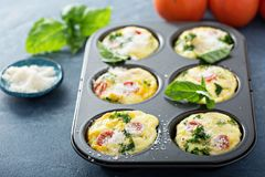 Healthy egg muffins, mini frittatas with tomatoes. And greens topped with grated parmesan stock photos