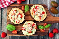 Healthy eggplant pizzas with melted mozzarella, tomatoes and basil Stock Photo