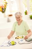 Healthy elderly woman eating salad. Happy elderly woman eating healthy salad at home. Looking at camera, smiling royalty free stock photos