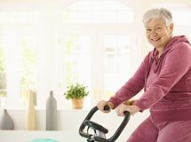 Healthy elderly woman on exercise bike Stock Images