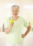 Healthy elderly woman holding apple. Looking at camera, smiling stock photo