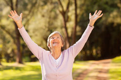 Healthy elderly woman. Looking up with arms outstretched outdoors Stock Image