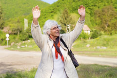 Healthy elderly woman looking up with arms outstretched outdoors. Positive senior  woman looking up with arms outstretched in the green  mountain Stock Photography