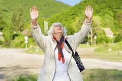 Healthy elderly woman looking up with arms outstretched outdoors. Positive senior  woman looking up with arms outstretched in the green  mountain Stock Photo