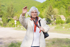 Healthy elderly woman smiling and waving. Positive senior  woman looking up with arms outstretched in the green  mountain Royalty Free Stock Images