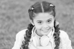 Healthy emotional happy kid relaxing outdoors. What makes child happy. Girl braids hairstyle and modern headphones enjoy. Relax. Secrets to raising happy child royalty free stock photo