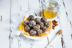 Healthy energy organic bites with nuts, dates, honey and sesame in a plate and centimeter on a light wooden background stock photo