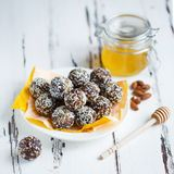 Healthy energy organic bites with nuts, dates, honey and sesame in a plate on a light wooden background royalty free stock photography