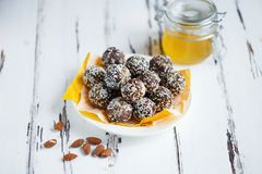 Healthy energy organic bites with nuts, dates, honey and sesame in a plate on a light wooden background stock image