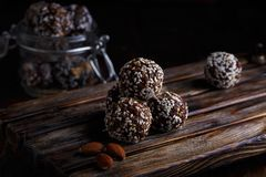 Healthy energy organic vegetarian bites with nuts, dates, honey and sesame on a dark wooden background stock photo