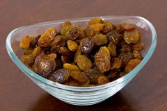 Dry and golden raisins in the bowl. Healthy and energy rich dry raisins in the bowl on the kitchen table Royalty Free Stock Photography