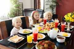 Healthy family breakfast for mother and kids. Healthy family breakfast at home. Mother and kids eating tropical fruit, toast bread, cheese and sausage. Children Royalty Free Stock Photo