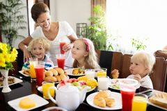 Healthy family breakfast for mother and kids. Healthy family breakfast at home. Mother and kids eating tropical fruit, toast bread, cheese and sausage. Children Royalty Free Stock Photography