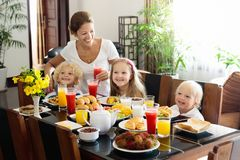 Healthy family breakfast for mother and kids. Healthy family breakfast at home. Mother and kids eating tropical fruit, toast bread, cheese and sausage. Children Royalty Free Stock Photos