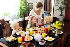 Healthy family breakfast for mother and kids. Healthy family breakfast at home. Mother and kids eating tropical fruit, toast bread, cheese and sausage. Children Stock Photo