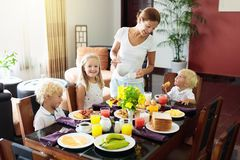 Healthy family breakfast for mother and kids. Healthy family breakfast at home. Mother and kids eating tropical fruit, toast bread, cheese and sausage. Children royalty free stock image