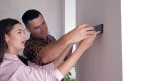 Healthy family couple improvement housing and hanging shelf on wall after repair in new apartment. Close-up stock video
