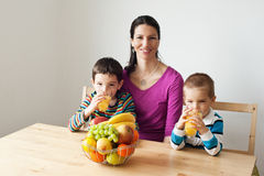 Healthy family drinking juice. Two children drinking juice for breakfast Stock Photography