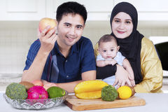 Healthy family with fresh fruits in kitchen Stock Images