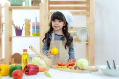 Healthy Family. Kid girl cooking and cutting vegetables for healthy care on kitchen. Daughter making cookie, so happy. Healthy and Family Concept royalty free stock photography