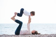 Healthy family playful pretty mother and child making exercises on autumn beach stock image