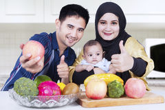 Healthy family showing thumbs-up in kitchen Stock Photos