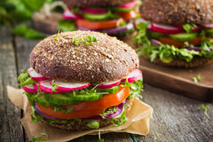 Healthy fast food. Vegan rye burger with fresh vegetables stock photo