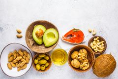 Healthy fat food background. Fish, nuts, oil, olives, avocado on white background, top view stock photo