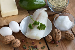 Healthy fats - fish, avocado, butter, eggs, nuts and seeds. Healthy fats - wild caught fish, avocado, butter, eggs, hemp seeds, walnuts, hazelnuts, pumpkin seeds royalty free stock photo