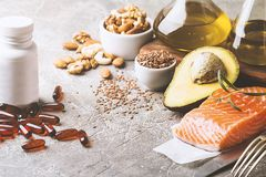 Healthy fats in nutrition. Salmon, avocado, oil, nuts. Concept of healthy food Royalty Free Stock Photos
