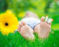 Healthy feet. Children feet in green grass. Butterfly on spring flower Stock Photos