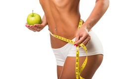 Healthy female body with apple and measuring tape Stock Image