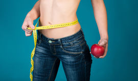 Healthy female body with apple and measuring tape. Healthy fitness and eating lifestyle concept. Stock Photos