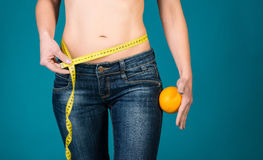Healthy female body with orange and measuring tape. Healthy fitness and eating lifestyle concept. Stock Photos